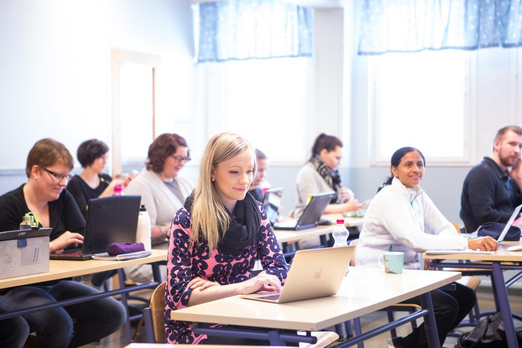 Ihmisiä luokkahuoneessa tietokoneiden ääressä
